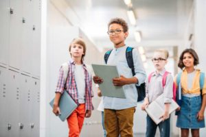 Image depicting children in a brightly lit school corridor.
