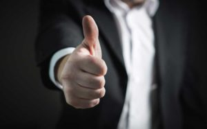 Stock Photography image of man in gray suit doing the thumbs up gesture.